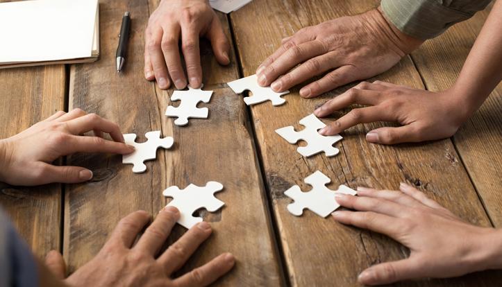 Mehrere Hände, die verschiedene Puzzlestücke zusammenschieben auf einem Tisch